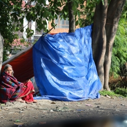 Old Nepali woman with tarpaulin shelter